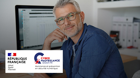 visuel pour Cybermailveillance : Homme souriant près de son ordinateur